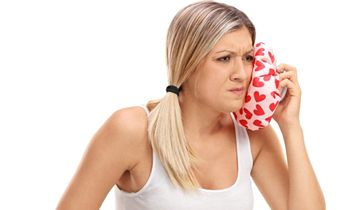 woman putting cold compress on face