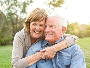 Older couple smiling together outside