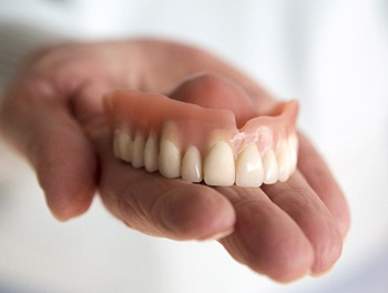 Person holding a full denture
