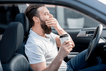 A man yawning in his car while holding a cup of coffee.