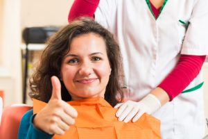 Smiling woman in dental chair giving thumbs up