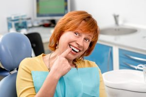 Senior woman in dental chair pointing to her smile
