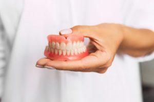 doctor holding dentures in Worthington