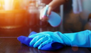 person sanitizing a countertop