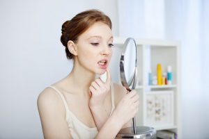 young woman looking at mouth in mirror to see if she'll need gum disease treatment in Worthington