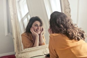 Woman looking in mirror at what teeth do