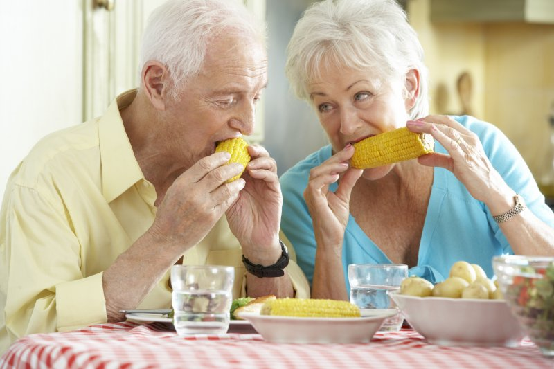two senior citizens eating corn on the cob