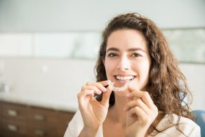 Woman holding clear aligner for Invisalign